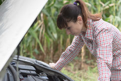 Woman trying to repair her broken car Royalty Free Stock Photo