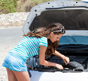 Woman is trying to repear her broken car Stock Photography
