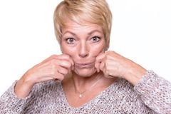 Woman trying to reverse the signs of aging. Attractive middle-aged woman with short blond hair trying to reverse the signs of aging by pulling on her cheeks with stock images