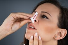 Free Woman Trying To Stop Nose From Bleeding Stock Photography - 182251482