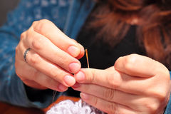 Woman  trying to thread a needle Stock Photos