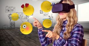 Woman trying to touch emojis while wearing VR glasses. Digital composite of Woman trying to touch emojis while wearing VR glasses Royalty Free Stock Images