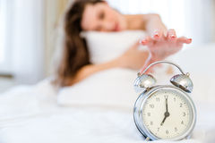 Woman trying to turn off the alarm clock Stock Images