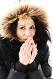 Woman trying to warm her hands with a breath Stock Photos