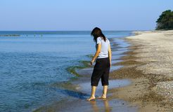 Woman trying water. A brunette woman in black trousers trying water temperature of the sea or ocean Stock Photo