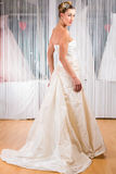Woman trying wedding dress in shop. Woman trying on wedding dress or bridal gown in wedding fashion store Royalty Free Stock Photos