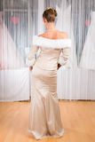 Woman trying wedding dress in shop. Woman trying on wedding dress or bridal gown in wedding fashion store Royalty Free Stock Images