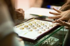 Woman trying wedding rings at a jeweller. Focus on rings Royalty Free Stock Photography