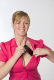Woman tucking mobile phone into her bra Stock Photo
