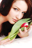 Woman with tulip. A young attractive woman with a red tulip lying on a white bed. High key stock images