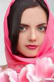 Woman with  tulip bouquet. Portrait of beautiful dark-haired woman with  tulip bouquet. girl covers her face with her handkerchief. Spring portrait Stock Photos