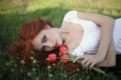Woman with tulip flowers. Beautiful young auburn haired woman lying in field with pink flowers Stock Photo