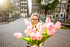 Woman with tulips in Amsterdam city. Woman giving a beautiful bouquet of pink tulips standing outdoors in Amsterdam city Royalty Free Stock Photography