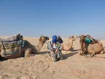 The woman in the turban, the face is closed, with a camel in the Sahara desert stock photos