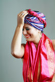 Woman in turban on her head. Young beautiful slim woman in turban on her head happy smiling and put hand on her head Royalty Free Stock Photography