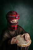 Woman in turban playing drum. Oriental woman in turban playing drum at green textured wall Stock Photos