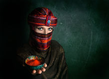 Woman in turban with red chili. Oriental woman in turban offering red chili powder at green textured wall Royalty Free Stock Image