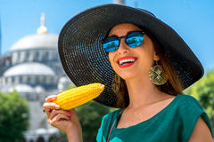 Woman with turkish corn. Young woman eating turkish boiled corn in Istanbul, Turkey. Traditional turkish street food Stock Photography