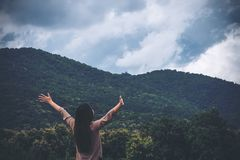 A woman turn back and stretched the arms with blue sky , green nature and mountain. Background stock image