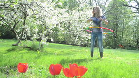 Woman turn hoop waist. Woman spin turn colorful hula hoop colorful ring on waist and back near beautiful blossom fruit tree and tulips stock video