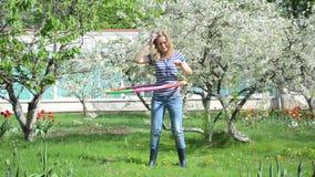 Woman turn hoop waist. Woman spin turn colorful hula hoop ring on waist near beautiful blossom fruit tree and tulips stock footage