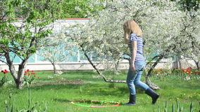 Woman turn hoop waist. Woman take and spin turn colorful hula hoop colorful ring on waist and back near beautiful blossom fruit tree and tulips stock video footage