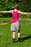 Woman turn spin hula hoop ring on waist in garden Royalty Free Stock Photo