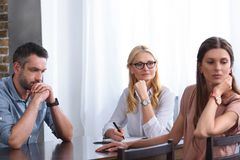 Woman turned away and her frustrated husband sitting at table on therapy session by female counselor. In office royalty free stock image