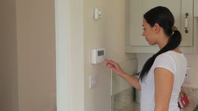 Woman turning on alarm system. In kitchen stock video
