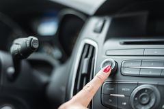 Woman turning on car radio Stock Image