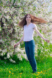 Woman turning head and smiling. Young girl turning head and smiling with blossom tree behind Royalty Free Stock Image