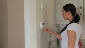 Woman turning on home alarm system. In kitchen stock footage