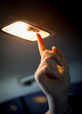 Woman turning light on in car salon Royalty Free Stock Image