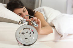Woman turning off alarm clock Royalty Free Stock Photography