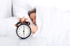Woman turning off the alarm clock. Bedtime collection: woman turning off the alarm clock Stock Image