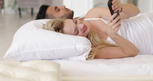 Woman turning off alarm clock cell phone lying in bed couple morning wake up smile stock video footage