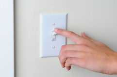 Woman turning off light switch Stock Image