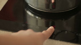 Woman turning on the oven stock footage