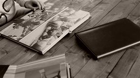 Woman reviewing pages of photo album. Woman turning the pages of a photo album, photography magazine stock footage