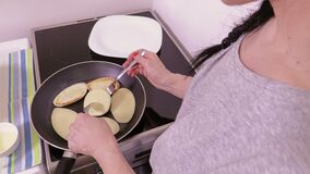 Woman turning pancakes on pan. In room stock footage