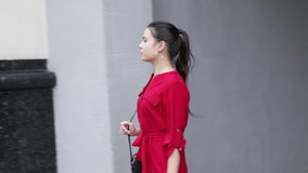 Woman turning round the corner in the city. Young woman in a red dress turning round the corner in the city stock video
