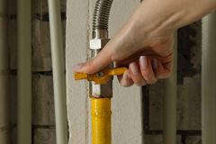 Woman turning on or turning off gas supply on yellow gas pipe royalty free stock images