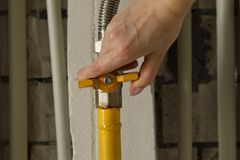 Woman turning on or turning off gas supply on yellow gas pipe stock photography