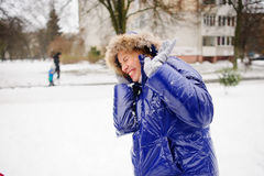 The woman turns aside from the snowballs flying to her. Royalty Free Stock Photo