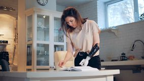 Handicapped woman turns pages with a robotic prosthesis, close up. Woman turns book pages, using a bionic hand
