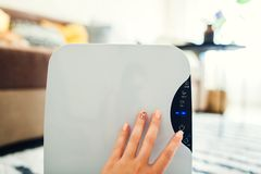 Woman turns dehumidifier on using touch panel at home. Modern airdryer device for cleaning air royalty free stock photo