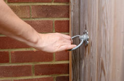 Woman turns a metal ring handle to open a gate Stock Photo