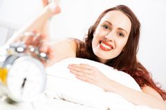 Woman turns off the alarm Stock Image