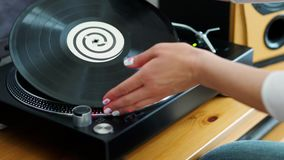 Woman turns off the turntable takes the LP