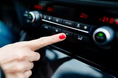 Woman Turns On Air Conditioning In The Car Royalty Free Stock Images